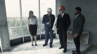 Man in suit, hard hat show woman, african american unfinished construction. Young couple, wife and husband buy house, new home for extended family. Male purchase flat in multi storey building for