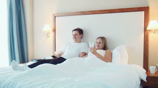 Man is watching TV while lying in bed and pretty blonde woman show him something on screen of smartphone