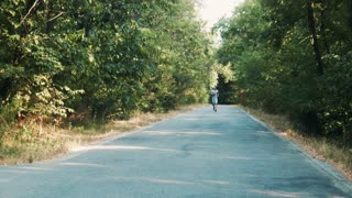 Man jogging along a woodland road approaching the camera from a distance in a fitness and healthy lifestyle concept
