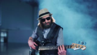 Man playing the bass guitar sitting in smoke while video production process