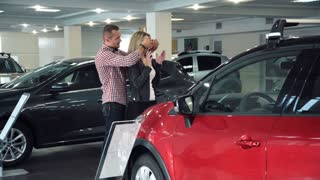 Man Standing Behind Woman and Covering Her Eyes While Standing in front of Shiny New Red Vehicle Inside Car Dealership - Man Surprising Woman with New Car in Show Room