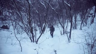 Man trying to find a way with GPS in a snowy forest