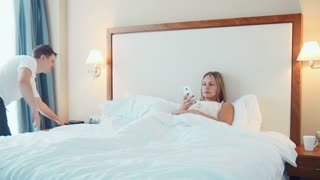 Man using remote control in bed with woman using her phone while under covers in hotel room