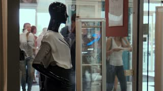 Mannequin on a show-window at a background people