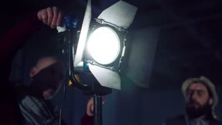 Men filmmakers adjusting professional light stand in studio together, with lighting on and blinking at camera