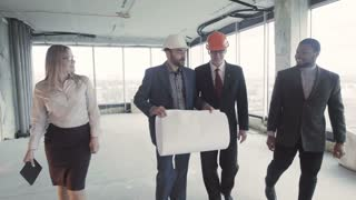 Men, woman in suit, hard hat move, communicate and discuss. Three white, one black smiling businessman and pretty female talk about successful good deal on buying house with rough finish, inside