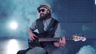 Middle shot of bearded man in sunglasses and hat wearing vest and shirt sitting on chair, playing black electric guitar and smiling in empty hall with studio lighting. Camera moving around