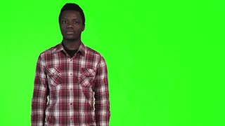 Modern african man pointing with both hands towards blank copy space on a bright green background, upper body side view