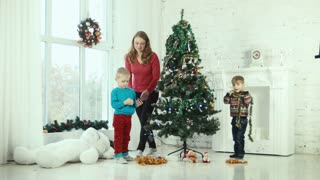 Mother and children decorate the Christmas tree