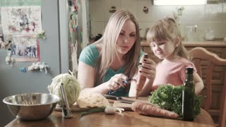 Mother at table showing how to peel carrot to her little cute daughter in kitchen using special knife tool.  Girl are so happy to learn how to cook healthy food