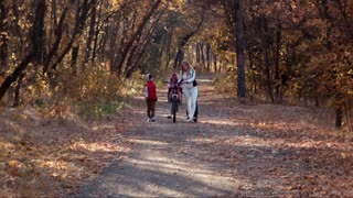 Mother walks in autumn park with children with bike