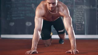 Muscular topless young man doing push ups in cross fit gym