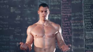 Muscular topless young man doing weightlifting exercises in cross fit gym