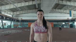 One caucasian sport female prepares for a throw of javelin on stadium. Woman go straight and looking on the camera