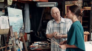 Pair of male and female skilled artists discussing a finished painting in art studio
