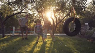 Parent playing with small two happy children at home on backyard with swing and trees during sunset