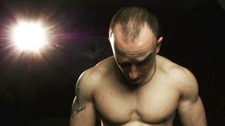 Portrait of muscular man looking at camera while opening katana