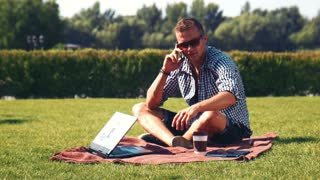 Portrait of smiling young man in sunglasses using smartphone and laptop with cup of coffee in sunny park