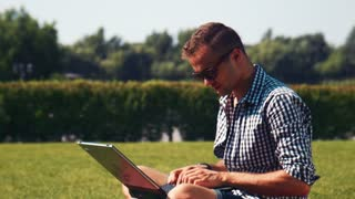 Portrait of young handsome man working on laptop in sunny park