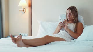 Pretty blonde woman wearing nighty lying in bed on white bedsheet and use smartphone and laughing