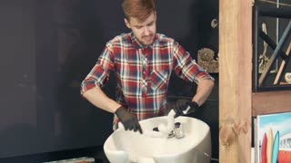 Professional barber squeezing hot water from towel