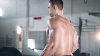 Rear side view on shirtless muscular Caucasian man exercising at large gym with light flare behind him