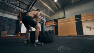 Rear view of strong man flipping tyre while practising in Crossfit gym