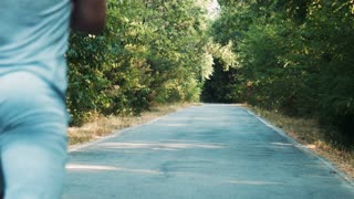 Rear view of unrecognizable sportsman running fast along asphalt road in countryside