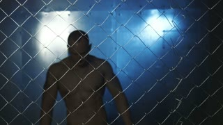 Sad bald topless man looking at camera while standing beyond wire fence in prison then looking down