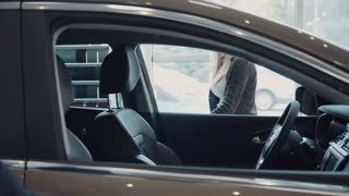 Sales manager gets in the car with the client and begins to tell her about the car. It shows the interior of the cabin and motivates her to buy this for car