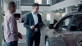 Salesman negotiating a contract with customers purchasing a new car leaning through the window with the paperwork. Or maybe customers sign an agreement for a test drive