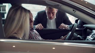 Salesman talking to customers in a new car in a motor showroom as they shop for a new vehicle leaning in through the open window