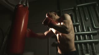 Side view of muscular man in red gloves boxing