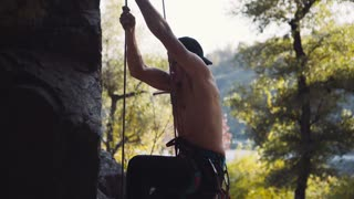 Side view of topless young climber in cap descending the cliff in park with rope