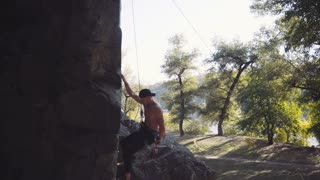 Side view of young climber ascending cliff with rope and carabiners against sky then he breaks down or fall