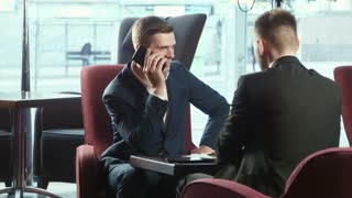 Two business discuss terms of contract and talking by smartphone