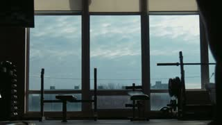 Silhouette of the attractive woman going on a fitness studio to a window