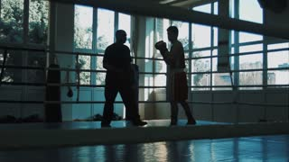 Silhouette of the trainer of the training young boxer on a ring