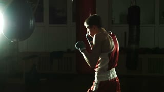 silhouette of Young boxer hitting punching bag in gym
