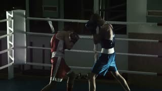 Silhouette training sparring of two boxers on a ring