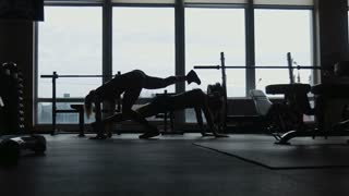 silhouette, two girls do push-ups together in a gym