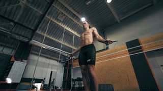 Single fit young man performing jump rope exercises at indoor gym with ropes and other equipment, round camera