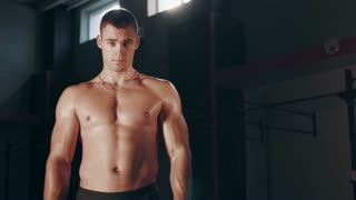 Single handsome muscular young adult man standing with shirt off in large indoor gym and looking at camera