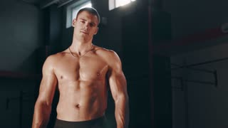 Single handsome muscular young adult man standing with shirt off in large indoor gym
