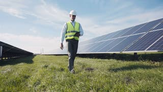 Single man in reflective green vest and white hard hat with digital tablet, walking near solar panels for concept about employment in alternative energy
