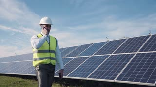Single man in reflective yellow vest and white hard hat with digital tablet, walking near solar panels for concept about employment in alternative energy and talk by phone