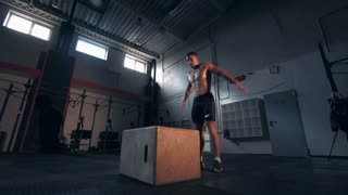 Single shirtless young man in dark shorts in motion doing jumping exercises in large gymnasium