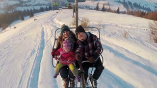skiers family riding up on ski lift and make selfie