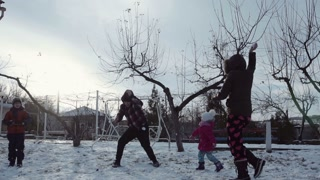 Slow motion happy family throw snow up in the air and laugh. Sheep dog running around