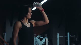 Slow motion of fit attractive woman pouring a water bottle on herself for refreshment
